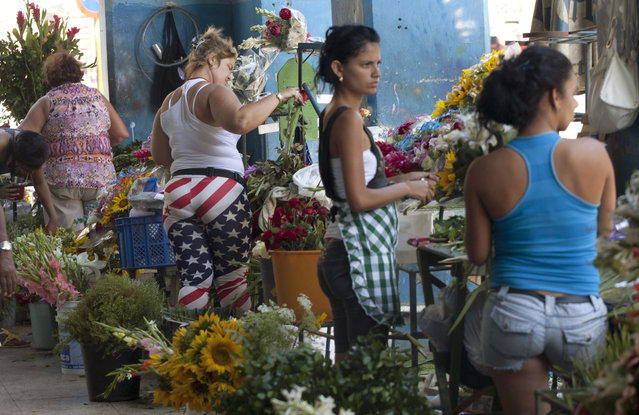 Women, one wearing pants made with the U.S flag colors,  work at their stalls selling flowers in Havana, Cuba, Thursday, April 9, 2015. (Photo by Desmond Boylan/AP Photo)