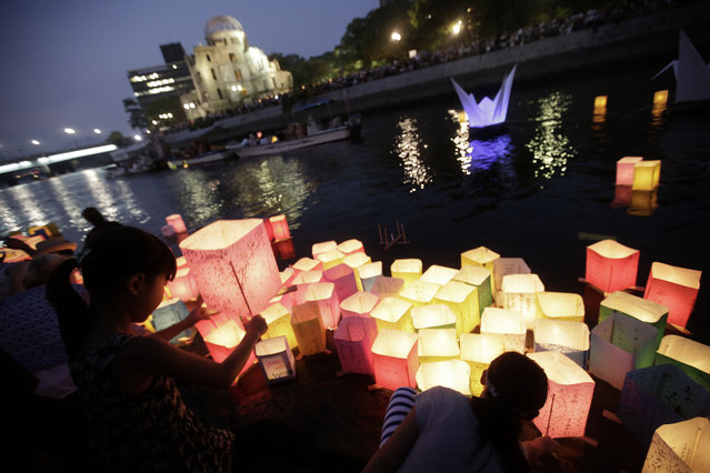 Children offer prayers as after releasing paper lanterns to the Motoyasu River where hundreds of thousands of atomic bombing victims died with the backdrop of the Atomic Bomb Dome in Hiroshima, western Japan Thursday, August 6, 2015. Japan marked the 70th anniversary Thursday of the atomic bombing of Hiroshima. (Photo by Eugene Hoshiko/AP Photo)