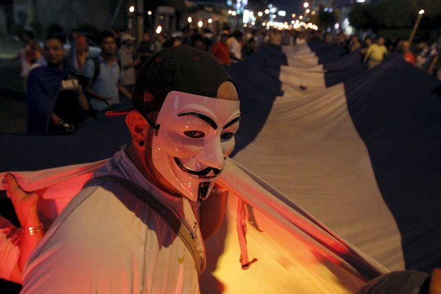 A demonstrator, wearing a Guy Fawkes mask, takes part in a march to demand the resignation of Honduras' President Juan Orlando Hernandez along the streets of Tegucigalpa, August 7, 2015. Thousands of protesters have been continuing demonstrations in Tegucigalpa, calling for the resignation of Hernandez over a $200 million corruption scandal at the Honduran Institute of Social Security. (Photo by Jorge Cabrera/Reuters)