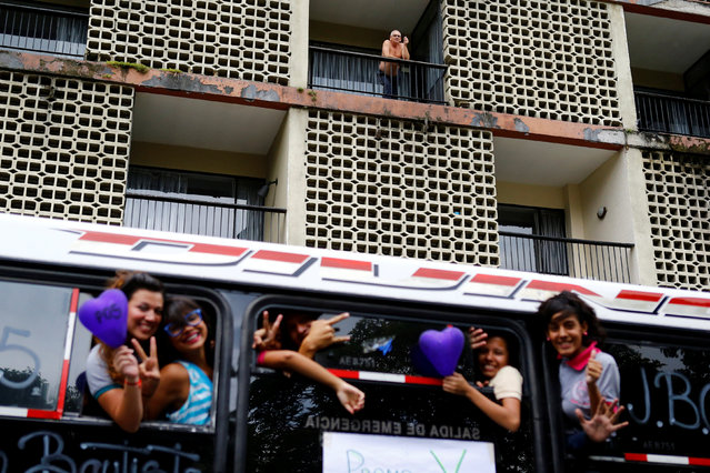 High school students gesture as they take a ride on a bus as a man smokes on a balcony in Caracas, Venezuela June 17, 2016. (Photo by Ivan Alvarado/Reuters)