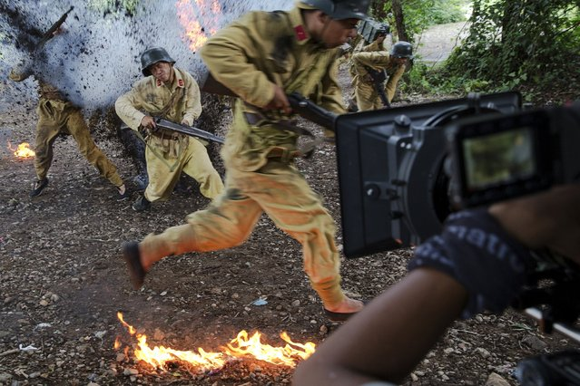 "The camera rolls as actors dressed as historical Chinese soldiers act as though they have been hit by artillery, during filming of ""The Last Prince"" television series on location near Hengdian World Studios near Hengdian July 24, 2015. (Photo by Damir Sagolj/Reuters)"