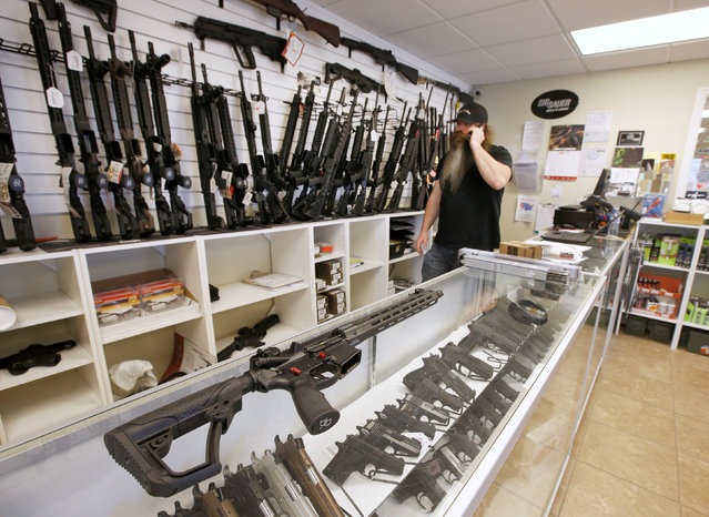 """An AR-15 sits on a display case as Willy Ludlow, owner of  the """"Ready Gunner"""" gun store in Provo, Utah, U.S., June 21, 2016. (Photo by George Frey/Reuters)"""