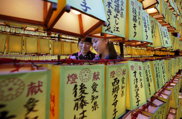 """Women walk in front of a row of paper lanterns with the names of the shrine deveotees, during the festival of """"Mitama"""" or departed souls, at Yasukuni shrine in Tokyo, Monday, July 14, 2014. The annual summer festival is held to solace the souls of the war dead. (Photo by Shizuo Kambayashi/AP Photo)"""