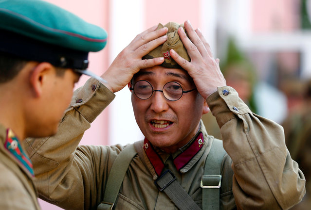 Japanese military enthusiast Iwahashi Kazuharu, dressed as a World War Two Red Army soldier, adjusts his hat as he marks the 75th anniversary of the Nazi Germany invasion, in Brest, Belarus June 21, 2016. (Photo by Vasily Fedosenko/Reuters)