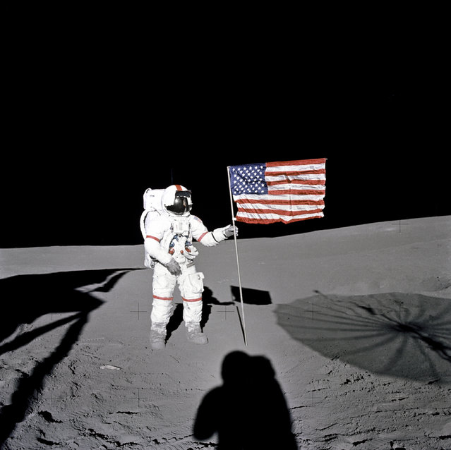 "Astronaut Alan B. Shepard Jr., Apollo 14 Commander, stands by the U.S. flag on the lunar Fra Mauro Highlands during the early moments of the first extravehicular activity (EVA-1) of the mission. Shadows of the Lunar Module ""Antares"", astronaut Edgar D. Mitchell, Lunar Module pilot, and the erectable S-band Antenna surround the scene of the third American flag planting to be performed on the lunar surface. (Photo by NASA)"