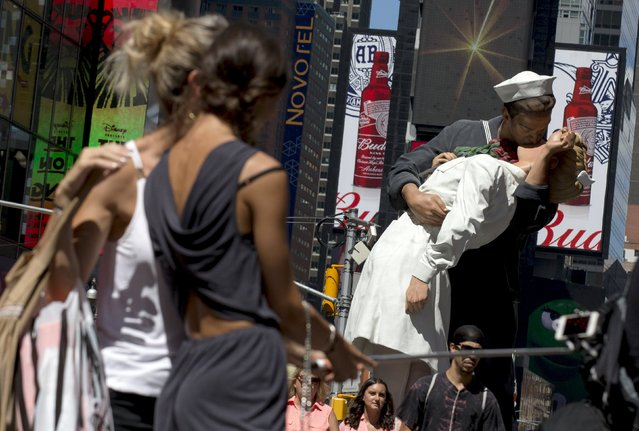 """Tourists take a """"selfie"""" photo near a replica sculpture of the famous photo by Alfred Eisenstaedt in New York's Times Square August 13, 2015. (Photo by Brendan McDermid/Reuters)"""