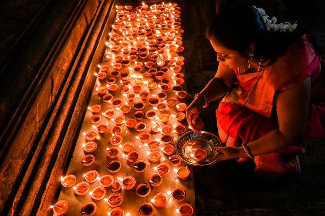 A Hindu devotee lights an oil lamp at a Hindu temple in Colombo, Sri Lanka on January 1, 2020. (Photo by Lakruwan Wanniarachchi/AFP Photo)