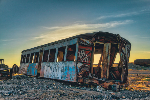 """Staring said: """"The sunset was spectacular and the sky exploded with the most intense colours I've ever seen. I stayed for a few hours to watch the sunset, climb around the rusting carcasses and taking as many photos as I could before walking back to town in the dark"""". (Photo by Chris Staring/Rex Features/Shutterstock)"""