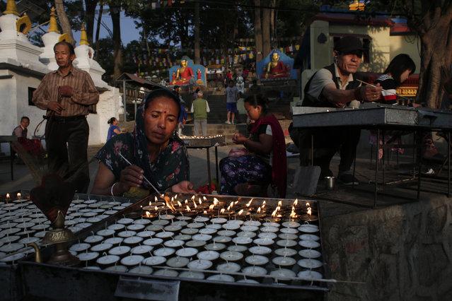 Buddhist worshippers light butter lamps during morning prayers in Swayambhunath stupa, Kathmandu, Nepal, Tuesday, June 13, 2017. Swayambhunath stupa is an ancient religious complex atop a hill also known as the monkey temple. (Photo by Niranjan Shrestha/AP Photo)