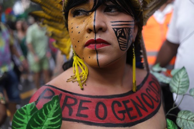"An indigenous woman with a Portuguese inscription that reads ""Stop the genocide"" on her body takes part in the ""Academicos do Baixo Augusta"" block party in Sao Paulo, February 16, 2020. (Photo by Rahel Patrasso/Reuters)"