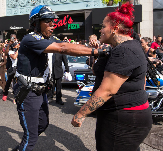 "A Boston Police officer pushes back counter-protesters on Boylston Street in Boston, Massachusetts, USA 19 August 2017. The counter-protesters were gathered in response to an ""alt-right"" ""Free Speech"" rally. (Photo by Matthew Healey)"