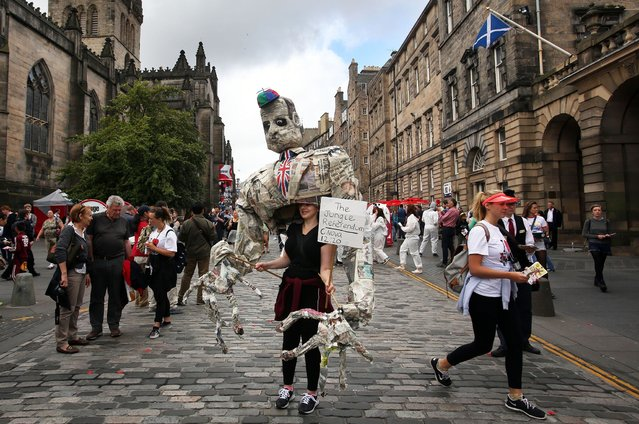 Edinburgh Festival acts play to the crowds on the Royal Mile, Edinburgh. (Photo by David Cheskin/PA Wire)