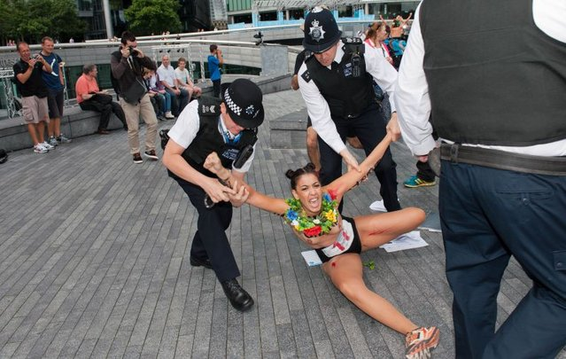 """British policemen block a topless activist of Ukraine's prominent feminist rights group FEMEN as she was protesting near the Tower Bridge in Central London on August 2, 2012 on day 6 of the London 2012 Olympic games. FEMEN's activists organised an """"islamic maraton"""" to demonstrate against """"islamic regimes"""" they say being supported by the International Olympic Committee. (Photo by Will Oliver/AP Photo)"""