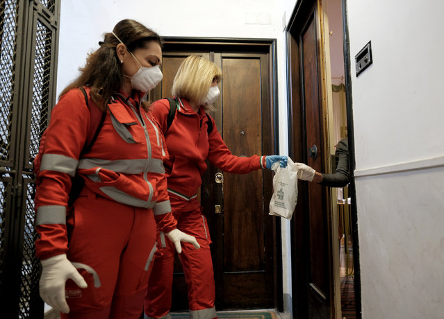 Red Cross personnel deliver medical supplies door to door, in Rome Friday, March 13, 2020. A sweeping lockdown is in place in Italy to try to slow down the spread of coronavirus epidemic. For most people, the new coronavirus causes only mild or moderate symptoms. For some, it can cause more severe illness, especially in older adults and people with existing health problems. (Photo by Mauro Scrobogna/LaPresse via AP Photo)