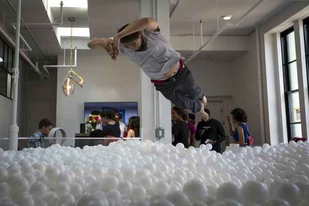 "A man dives into the ""JumpIn!"" ball pit, an interactive art installation by creative agency Pearlfisher made up of 81,000 white balls, in New York City August 25, 2015. (Photo by Mike Segar/Reuters)"