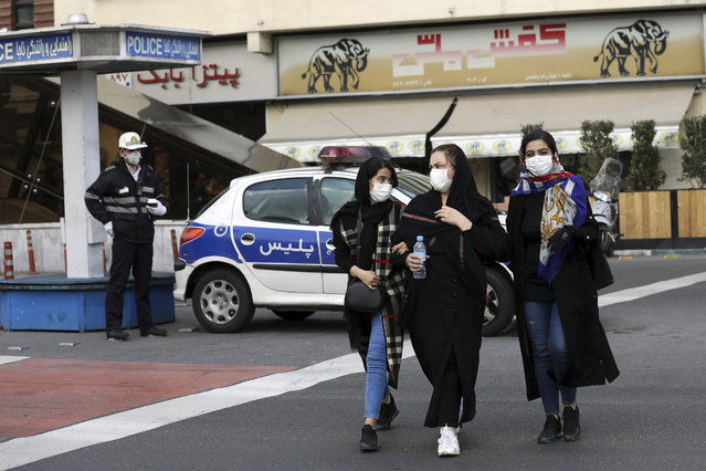 A policeman and pedestrians wear masks to help guard against the Coronavirus, in downtown Tehran, Iran, Sunday, February 23, 2020. On Sunday, Iran's health ministry raised the death toll from the new virus to 8 people in the country, amid concerns that clusters there, as well as in Italy and South Korea, could signal a serious new stage in its global spread. (Photo by Ebrahim Noroozi/AP Photo)