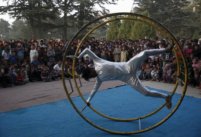 People watch a performance by a member of Afghan Mobile Mini Circus for Children (MMCC) during MMCC's festival in Kabul, Afghanistan August 14, 2015. (Photo by Ahmad Masood/Reuters)