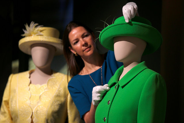 """Curator Caroline de Guitar, poses for photographers next to Britain's Queen Elizabeth's green ensemble worn for Trooping the Colour in 2016 marking her official 90th birthday, ahead of the opening of an exhibition entitled """"Fashioning a Reign: 90 Years of Style from the Queen's Wardrobe"""", at Buckingham Palace, in London, Britain July 21, 2016. (Photo by Peter Nicholls/Reuters)"""