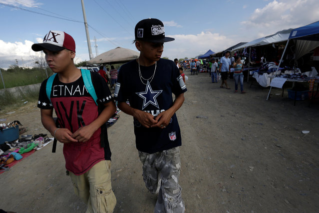 "Jaziel and Plasma, both attending the meetings of Raza Nueva in Christ, a project of the archdiocese of Monterrey, tour a flea market in the municipality of Juarez, on the outskirts of Monterrey, Mexico, June 25, 2016. In the troubled fringes of the northern Mexican city of Monterrey, an aspiring priest is using his faith to reach out to young gang members and at-risk youth, and bring them into his ""Gang of Christ"". (Photo by Daniel Becerril/Reuters)"