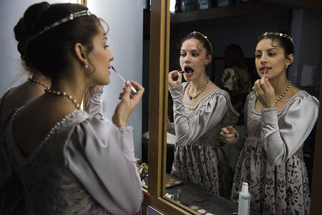 In this Friday, September 15, 2017 photo, ballet dancers from Uruguay's National ballet of the Sodre put on lipstick before a dress rehearsal for Romeo and Juliet in Montevideo, Uruguay. Dancers practice Monday through Friday for eight hours at a time. (Photo by Matilde Campodonico/AP Photo)