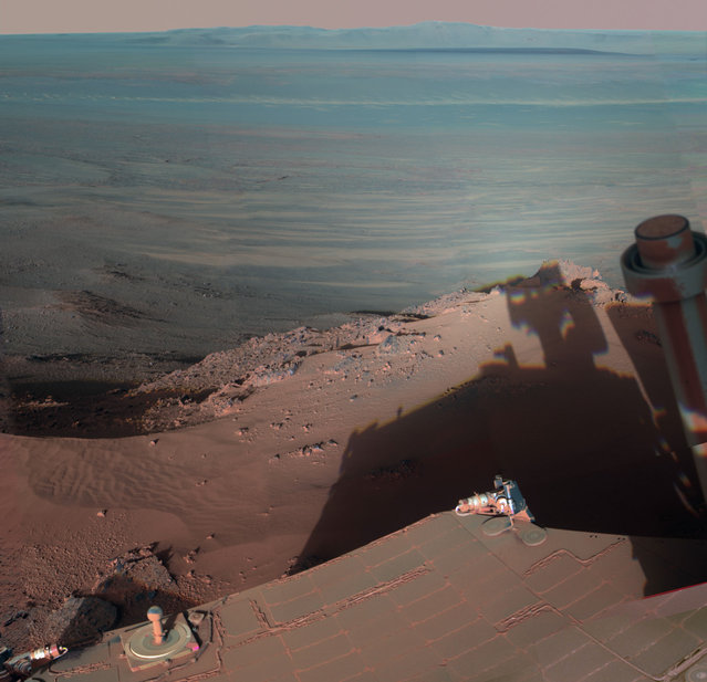 On Mars, NASA's Rover Opportunity catches its own late-afternoon shadow in this dramatically lit view eastward across Endeavour Crater. The rover used the panoramic camera (Pancam) between about 4:30 and 5:00 p.m. local Mars time to record images taken through different filters and combined into this mosaic view. Most of the component images were recorded during the 2,888th Martian day, or sol, of Opportunity's work on Mars (March 9, 2012). At that time, Opportunity was spending low-solar-energy weeks of the Martian winter at the Greeley Haven outcrop on the Cape York segment of Endeavour's western rim. Opportunity has been studying the western rim of Endeavour Crater since arriving there in August 2011. This crater spans 14 miles (22 kilometers) in diameter, or about the same area as the city of Seattle. (Photo by NASA/JPL-Caltech/Cornell/Arizona State Univ.)