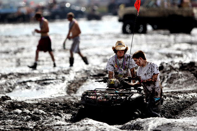 An ATV gets trapped in the mud bog. Many people underestimate the depth of the mud and get stuck. (Photo by Gary Coronado/The Palm Beach Post)