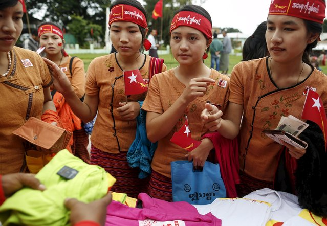 Ethnic Intha women buy shirts with National League for Democracy (NLD) party logo as they wait for the arrival of pro-democracy leader Aung San Suu Kyi at the Hopong township in Shan state, Myanmar September 6, 2015. (Photo by Soe Zeya Tun/Reuters)