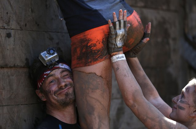 "Participants climb over a wall at the ""Tough Mudder"" endurance event series in Arnsberg September 6, 2014. Competitors who took part in the endurance event saw themselves having to overcome various military style obstacles. (Photo by Ina Fassbender/Reuters)"