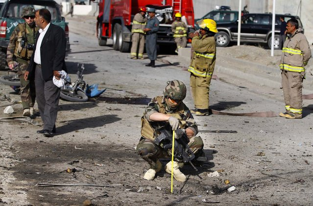 A French soldier investigates the scene of a suicide bombing in Kabul, Afghanistan, on September 18, 2012. A suicide bomber rammed a car packed with explosives into a mini-bus carrying foreign aviation workers to the airport in the Afghan capital killing at least nine people in an attack a militant group said was revenge for an anti-Islam film that ridicules the Prophet Muhammad. (Photo by Ahmad Jamshid/Associated Press)