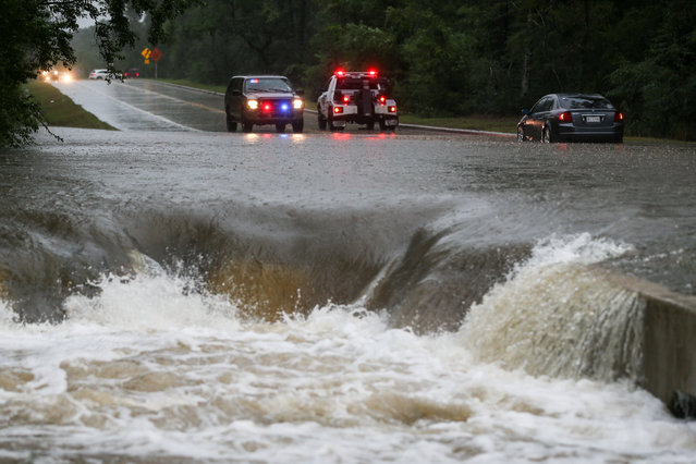 A police officer directs traffic away after a car is stranded in flash flooding on Friday, September 19, 2014, on Research Forest Drive in The Woodlands, Texas. (Photo by  Michael Minasi/AP Photo/The Courier)