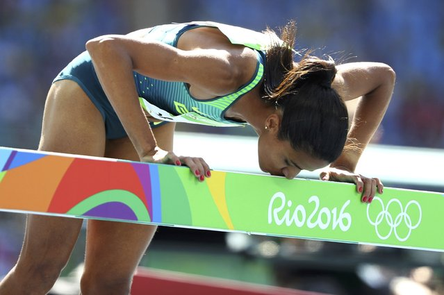 2016 Rio Olympics, Athletics, Preliminary, Women's 3000m Round 1, Olympic Stadium, Rio de Janeiro, Brazil on August 13, 2016. Juliana Paula dos Santos (BRA) of Brazil kisses a hurdle after the race. (Photo by Lucy Nicholson/Reuters)