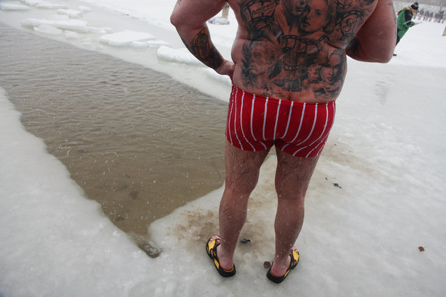 A tatooed participant relaxes after taking a quick dip in frozen Orankesee lake at the 26th annual Berlin Seals winter swim on January 9, 2010 in Berlin, Germany. Approximately a dozen ice swimming clubs joined the annual event as a chilly snowstorm swept across Germany. (Photo by Sean Gallup)