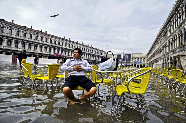 A tourist sits outside flooded a cafe in St. Mark square as high tides rose 3 feet above sea level, partly flooding the city of Venice, Italy October 15, 2012. (Photo by Luigi Costantini/Associated Press)