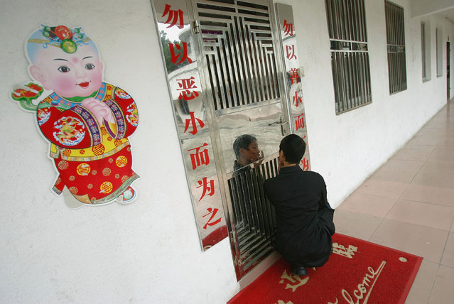 A kid looks himself in a door at an assistance center February 23, 2005 in Shenzhen, Guangdong Province, China. (Photo by Cancan Chu/Getty Images)