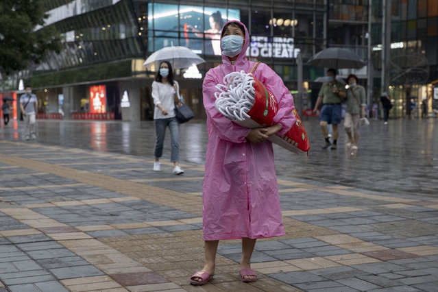 A woman wearing a face mask to curb the spread of the coronavirus takes the opportunity to sell umbrellas as it rains in Beijing on Thursday, June 18, 2020. A new coronavirus outbreak in Beijing saw a decline in daily cases Thursday while the United States increased pressure on China's leaders to reveal what they know about the pandemic. (Photo by Ng Han Guan/AP Photo)