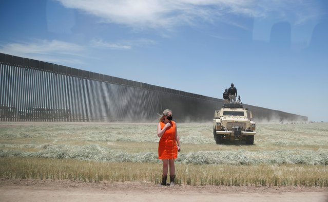 A white House staff member watches President Donald Trump's motorcade arrive as U.S. Secret Service counter assault team (CAT) snipers stand watch atop a U.S. border patrol armored tactical as the president arrives to tour a recently constructed section of U.S.-Mexico border wall on the border in San Luis, Arizona, June 23, 2020. (Photo by Carlos Barria/Reuters)