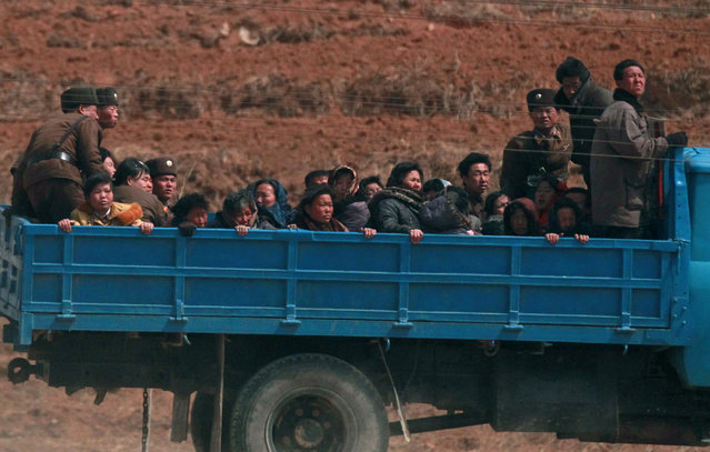 Villagers travel in a truck in a field northwest of Pyongyang, April 8, 2012. (Photo by Bobby Yip/Reuters)