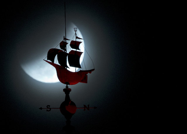 The Earth's shadow begins to fall over the moon during a total lunar eclipse, behind a weathervane shaped like a Spanish galleon on the Freedom Tower in Miami, Wednesday, October 8, 2014. (Photo by Wilfredo Lee/AP Photo)