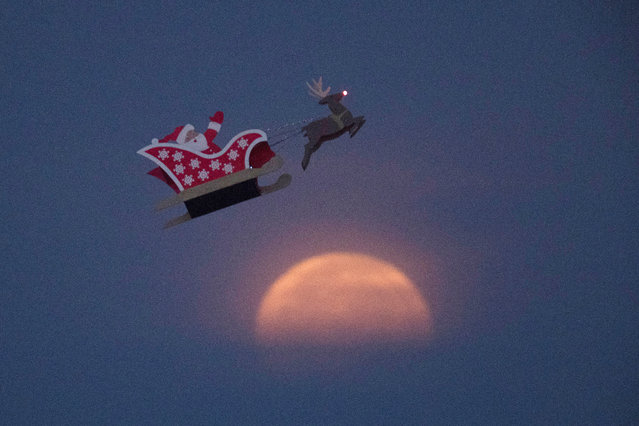 A 10-foot long remote controlled flying Santa makes a test flight past a setting moon over the ocean in Carlsbad, California, U.S., December 3, 2017. (Photo by Mike Blake/Reuters)