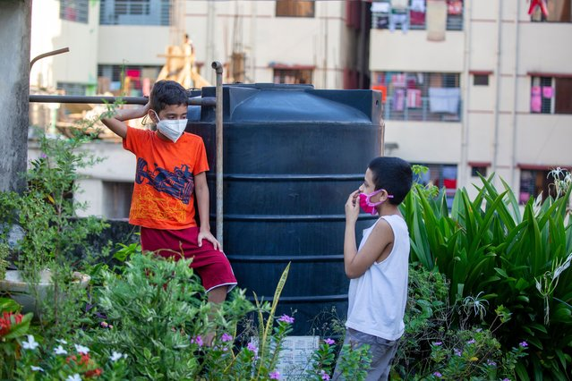 Bangladeshi child's wears a face mask as they talk to their rooftop at the residential area in Dhaka, Bangladesh 20 June 2020. Countries around the world are taking increased measures to stem the widespread of the SARS-CoV-2 coronavirus which causes the COVID-19 disease. (Photo by Monirul Alam/EPA/EFE/Rex Features/Shutterstock)