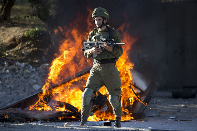 Israeli soldier stands during clashes with Palestinians following a protest against U.S. President Donald Trump's decision to recognize Jerusalem as the capital of Israel in the West Bank City of Nablus, Friday, December 8, 2017. (Photo by Majdi Mohammed/AP Photo)