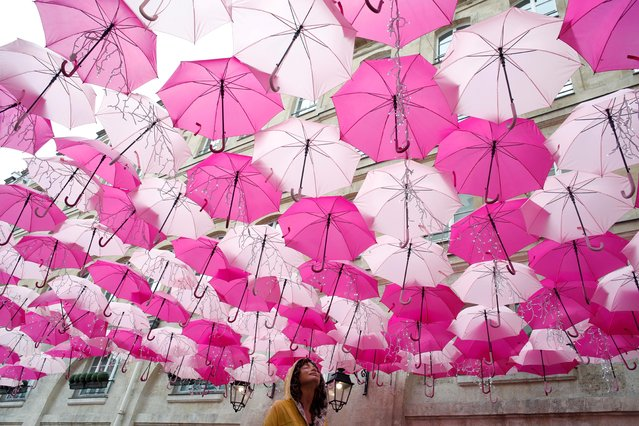 """An installation entitled """"Umbrella Sky Project"""" created by Portuguese artist Patricia Cunha and composed with pink umbrellas is pictured in Paris, France, March 11, 2020. (Photo by Benoit Tessier/Reuters)"""