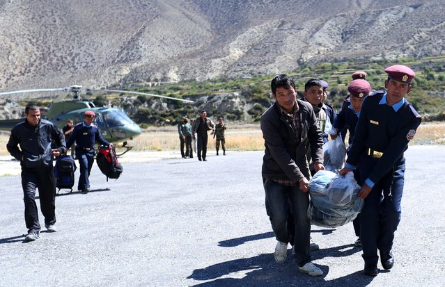 Nepalese police move the bodies of trekkers killed following a snowstorm and an avalanche to a plane to be transported to Kathmandu in Jomsom on October 17, 2014. Nepal's prime minister has pledged to set up a weather warning system after a major Himalayan snowstorm killed 32 people at the height of the trekking season, 17 of them tourists. (Photo by Skanda Gautam/AFP Photo)