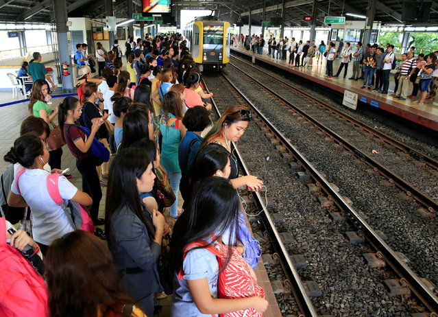 Commuters wait for a passenger coach of the Light Rail Transit System (LRT) at the central station in Metro Manila, Philippines June 21, 2016. (Photo by Romeo Ranoco/Reuters)
