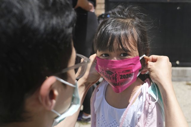 In this June 10, 2020, file photo, Olivia Chan's father helps her with a new mask she received during a graduation ceremony for her Pre-K class in front of Bradford School in Jersey City, N.J. As the Trump administration pushes full steam ahead to force schools to resume in-person education, public health experts warn that a one-size-fits-all reopening could drive infection and death rates even higher. (Photo by Seth Wenig/AP Photo/File)