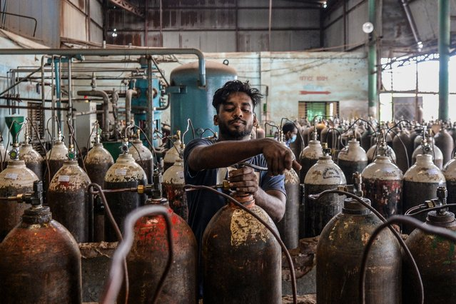 A worker refills medical oxygen cylinders at a refill plant in Narayanganj, on the outskirts of Dhaka on June 27, 2020. (Photo by Munir Uz Zaman/AFP Photo)