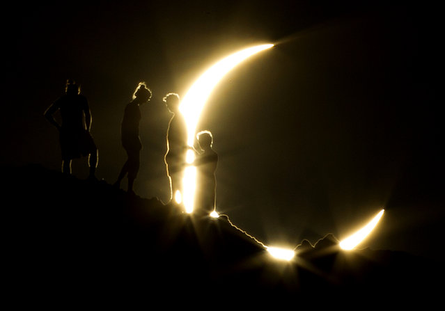 Hikers watch an annular eclipse from Papago Park in Phoenix on Sunday, May 20, 2012. The annular eclipse, in which the moon passes in front of the sun leaving only a golden ring around its edges, was visible to wide areas across China, Japan and elsewhere in the region before moving across the Pacific to be seen in parts of the western United States. (Photo by Michael Chow, The Arizona Republic/AP Photo)