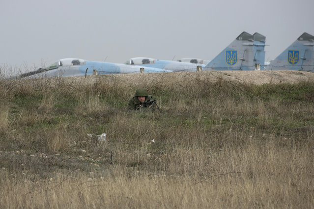 A Russian soldier lies with his back to Ukrainian fighter jets as he watches Ukrainian serviceman at the Belbek airport in the Crimea region, March 4, 2014. (Photo by Baz Ratner/Reuters)
