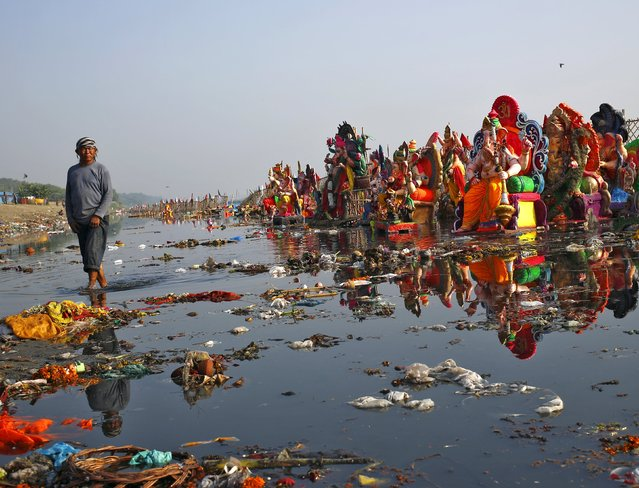 A man looks on as he collects items thrown by devotees as religious offerings next to idols of the Hindu god Ganesh, the deity of prosperity, after the idols were immersed on Sunday, in the waters of the Yamuna river in New Delhi, India, September 29, 2015. (Photo by Anindito Mukherjee/Reuters)