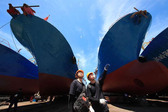 Surveyors inspect ships during the closed fishing season at a shipyard on July 29, 2020 in Xiangshan County, Zhejiang Province of China. (Photo by Zhang Peijian/VCG via Getty Images)